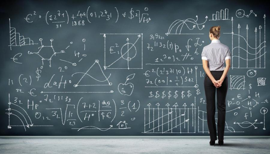 Thi is an image of a woman looking at maths on a chalk board. Signifying that diversity training should be fun and engaging.rsity training